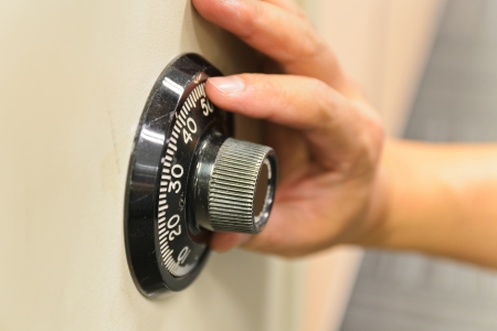 Hand opening a safe.