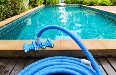 Pool vacuum cleaning flexible hose on the pool photo