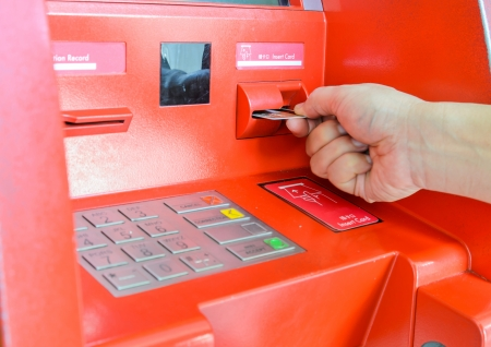 Hand inserting ATM card in ATM machine