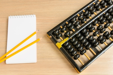 Ancient Chinese abacus,notebook,pencil on wooden background photo