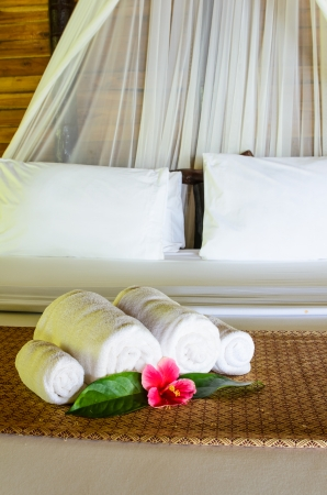 Welcome white towel  and flower on bed photo