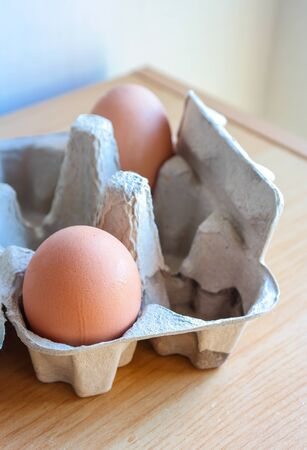 Eggs in paper tray on wooden  photo