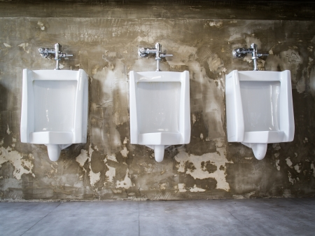 Urinal mounted on old wall background