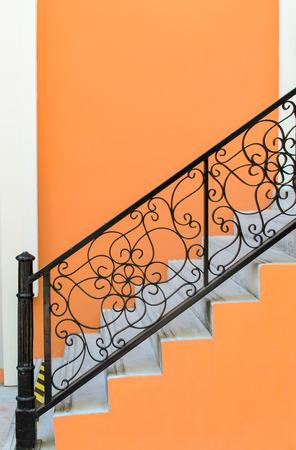 オレンジ色の壁の背景の柵と階段