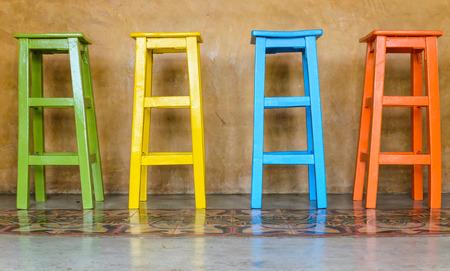 muebles antiguos: Sillas de madera de colores dispuestos de altura.