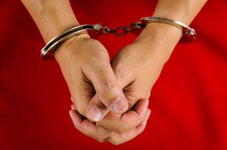 sadistic: Hand of a man with handcuff on red background
