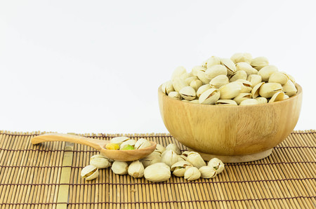 Pistachio nuts with wooden bowl on mat