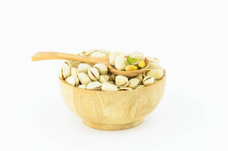 Pistachio nuts on wooden spoon with white  background