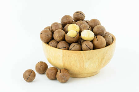 Macadamia Nuts  in wooden bowl on white background Stock Photo
