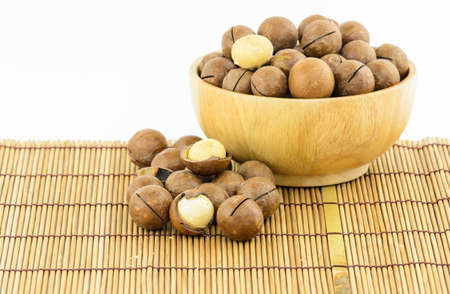 Macadamia Nuts on wooden mat and in wooen bowl