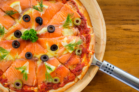 Pizza with smoked salmon on wooden table