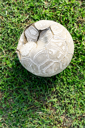Old football on grass field. Stock Photo