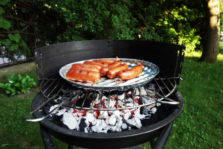 sizzle: Grilling sausages in the garden. Barbecue.