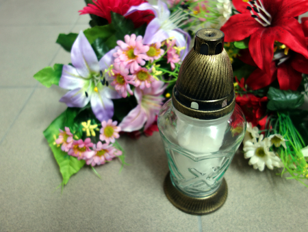 to pass away: Memorial grave candle and flowers
