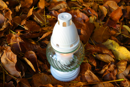 christian halloween: Lonely memorial candle at autumn cemetery Stock Photo