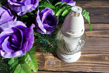 all souls' day: Blue roses and votive candle close view Stock Photo