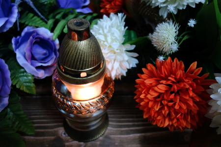 Memorial candle in glass and wreaths, funeral ceremony
