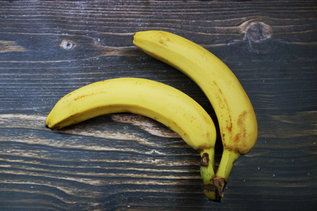 importation: Bananas on wooden desk, healthy tropical fruits, view from overhead