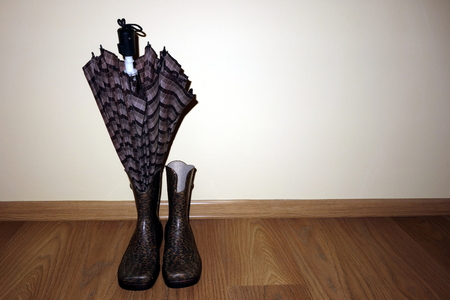 Pair of wellingtons and an umbrella on a bright wall background with copy space