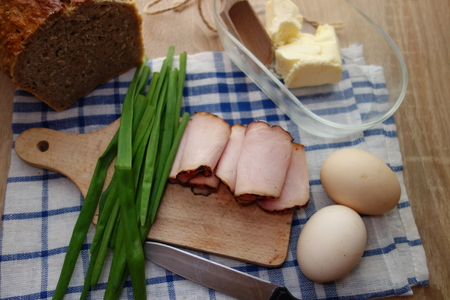 Eggs, ham, bread, butter and chives on wooden table