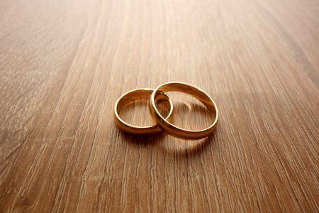 Two golden wedding rings on rustic wooden background