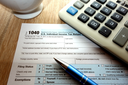 US 1040 tax form, calculator and pen on desk Stock Photo