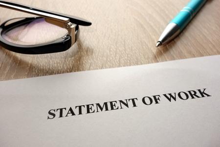 Statement of work, pen and glasses on desk Reklamní fotografie