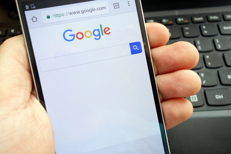 KONSKIE, POLAND - MAY 06, 2018: Man holding his smartphone with Google search browser displayed