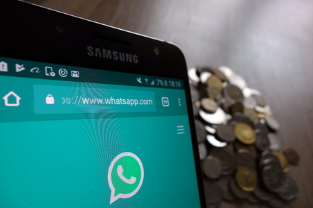 KONSKIE, POLAND - MAY 14, 2018: WhatsApp website is displayed on Samsung smartphone and stack of coins Editorial