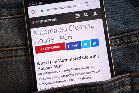 KONSKIE, POLAND - JUNE 11, 2018: An article about automated clearing house (ACH) on Investopedia website displayed on smartphone hidden in jeans pocket Редакционное