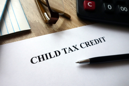 Child tax credit document with pen, calculator and glasses on desk