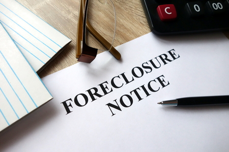 Foreclosure notice with pen, calculator and glasses in office