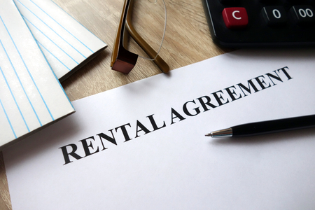 Rental agreement form with pen, calculator and glasses on desk