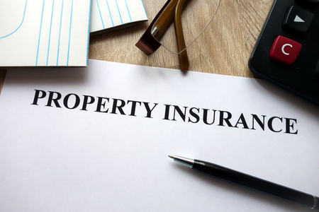 Property insurance document with pen, calculator and glasses on desk