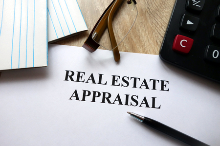 Real estate appraisal document with pen, calculator and glasses on desk Reklamní fotografie