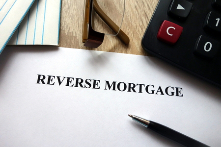 Reverse mortgage document with pen, calculator and glasses on desk