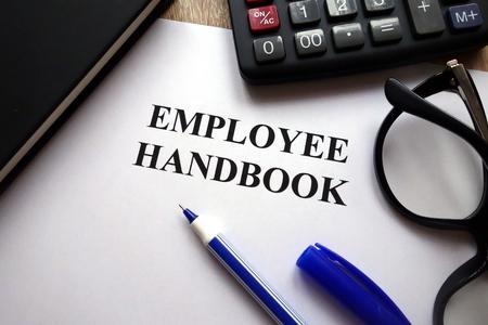 Employee handbook, pen, glasses and calculator on desk