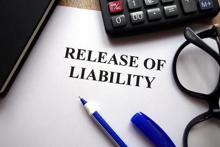 Release of liability document, pen, glasses and calculator on desk Reklamní fotografie