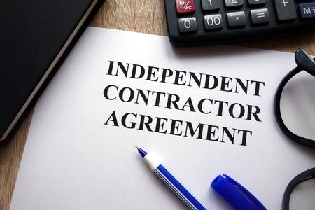 デスク上の独立した請負業者契約、ペン、メガネ、電卓