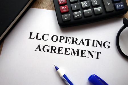 LLC operating agreement, pen, glasses and calculator on desk