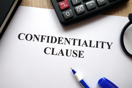 Confidentiality clause document, pen, glasses and calculator on desk Standard-Bild - 115244389