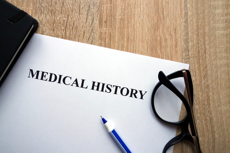 Medical history document, pen and glasses on desk