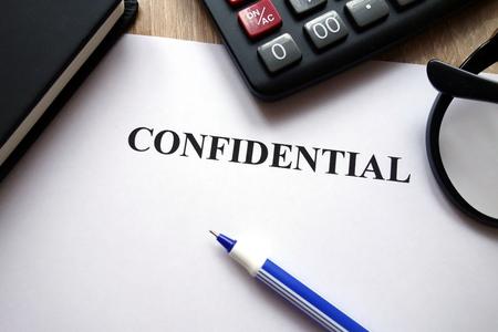 Confidential document, calculator, pen and glasses on desk