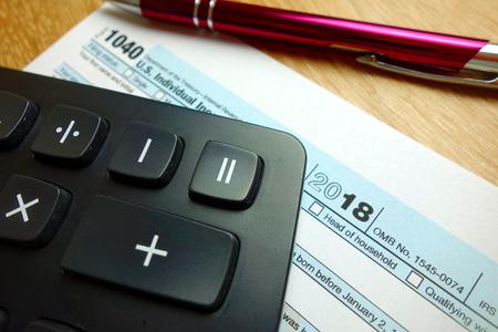 Form 1040, calculator and pen on desk, tax season 2019 concept Standard-Bild