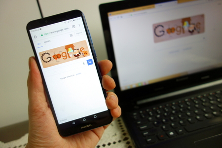 KONSKIE, POLAND - February 08, 2019: Google search website on Huawei smartphone with laptop on background. Digital device using concept Editorial