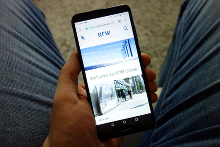 KONSKIE, POLAND - February 08, 2019: Man holding Huawei smartphone with KfW bank website displayed. Online banking concept Editorial