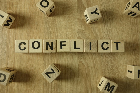 Conflict word from wooden blocks on desk