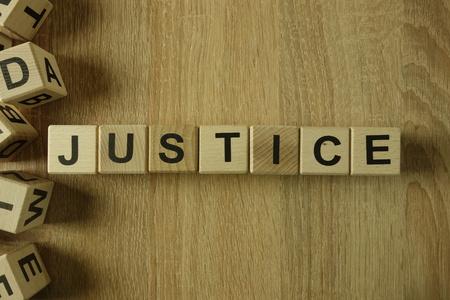 Gerechtigkeitswort aus Holzklötzen auf dem Schreibtisch