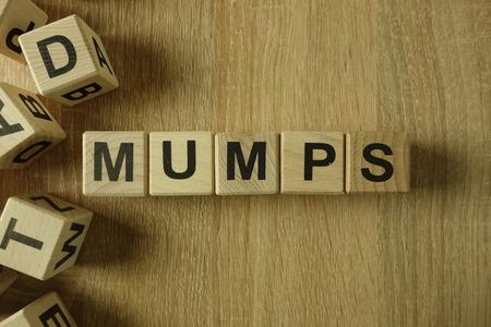 Mumps word from wooden blocks on desk Reklamní fotografie