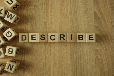 Describe word from wooden blocks on desk